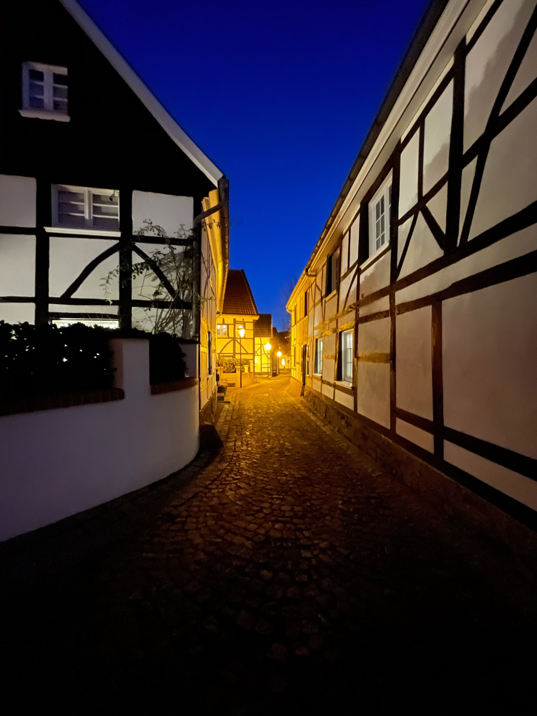 Narrow cobblestone street with framework houses on either side, shot at night with a dark blue sky and yellow lights in the distance.